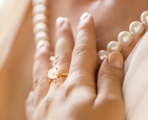 Close-up Of A Bride's Hand With Diamond Ring Touching Pearl Necklace